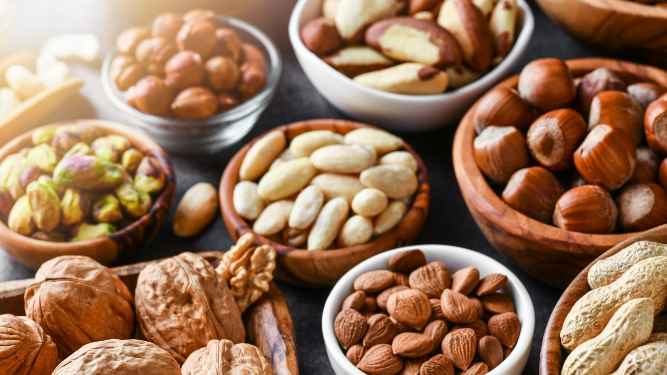 Mixed nuts in wooden bowls on black stone table. Almonds, pistachio, walnuts, cashew, hazelnut. Top view nut photo.